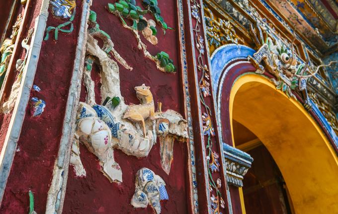 Một tour tham quan kinh thành Huế có hướng dẫn viên sẽ kết thúc tại cổng Hiển Nhơn, một trong bốn cánh cổng dẫn vào Đại Nội Huế, nằm ngay gần Phủ Nội Vụ. Trong ảnh là những chi tiết đắp ghép bằng mảnh sành đặc trưng trong cách trang trí tại Đại Nội mới được trùng tu.