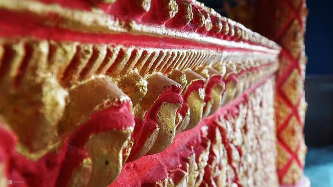 Bao quanh tượng Phật là những chi tiết chạm trổ sắc sảo với màu sắc sặc sỡ.