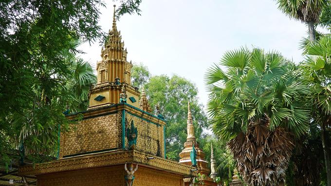 """Bên ngoài điện chính là hàng dài tháp đựng cốt của Phật tử nép mình dưới tán cây thốt nốt. Các ngôi tháp có nhiều kích cỡ khác nhau, thể hiện điều kiện của mỗi gia đình.Ông Chau Phol làm công quả ở đây hơn 50 năm cho hay, ngôi chùa vẫn giữ nguyên kiến trúc xưa. """"Chúng tôi vừa cho khánh thành một gian nhà dùng để đãi khách và tổ chức các lễ hội trong năm"""", ông nói."""