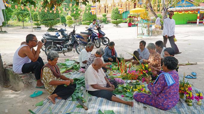 Theo nghi thức truyền thống của người Khmer, cứ đến lễ hội hoặc dịp đặc biệt, người dân và Phật tử sẽ cùng đến chùa để chuẩn bị. Trong ảnh là hoạt động làm hoa thủ công từ bắp chuối để trang trí trong lễ khánh thành gian nhà mới của chùa.