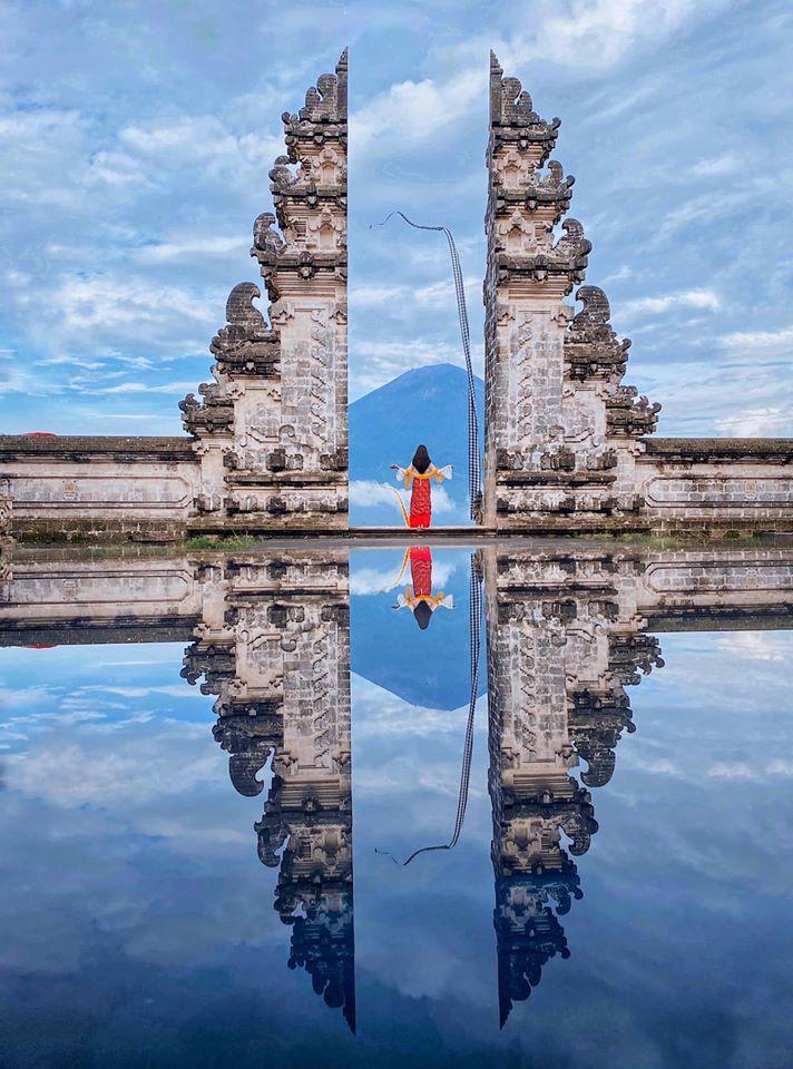 """Cổng trời Lempuyang Temple. Khi đến đây trời mưa lâm râm, bầu trời u ám mịt mù, mây che hết núi. Nhưng may mắn đến lúc tụi mình chụp lại trời xanh rất đẹp. Muốn có hình đẹp ở đây phụ thuộc vào yếu tố may mắn 😂. Và không có cái hồ nước nào đâu nhé, nó ảo vậy là do người ta để cái gương ở dưới rồi chụp. Nên lên Instagram mục """"địa điểm"""" để tham khảo trước các pose dáng. Mỗi người được chụp 3 tư thế khác nhau, rất nhanh nên không có thời gian suy nghĩ đâu 😭"""