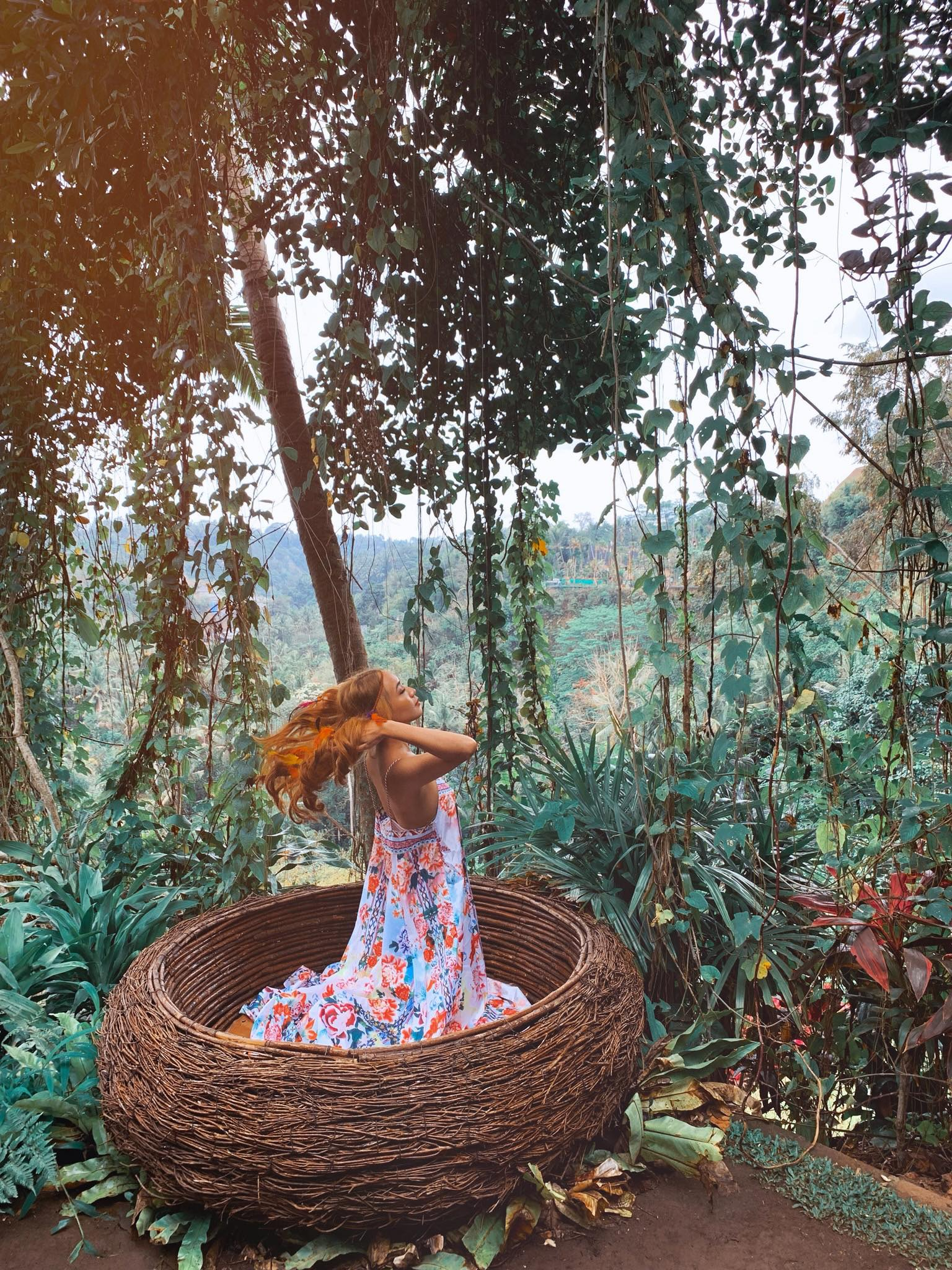 """Bali swing – tổ chim huyền thoại (các bạn nhớ mặc đồ lộng lẫy để chụp hình siêu đẹp nhé) Bali Swing chính là một trò """"đu dây"""" được nối ở 2 đầu trên thân cây dừa. Yên tâm là chúng ta có dây bảo hộ nữa nhé. Ở Bali Swing, có ba mức lựa chọn cho chiếc xích đu mà bạn có thể thử với các chiều cao khác nhau là 5 mét, 15 mét và 20 mét.  Trước khi chơi, bạn hãy chuẩn bị sẵn cho mình một bộ quần áo lộng lẫy nhé. Ở đây cũng có cho thuê váy để chụp hình đó! Đặc biệt đối với các bạn nữ nên lựa một chiếc váy thật đẹp cho mình. Váy có tà dài, thướt tha, màu sắc rực rỡ thì sẽ cực hợp concept và đảm bảo cực ảo (Mình chọn váy hoa lá hẹ cành bông chim bướm.  Ngoài swing, còn có cả những """"tổ chim"""" phục vụ cho nhu cầu chụp ảnh sống ảo. Đây cũng là một đặc trưng của Bali. Những tổ chim này được đầu tư thiết kế rất sống động. mình đã """"hoá bướm"""" đậu vào tổ chim chụp hình."""
