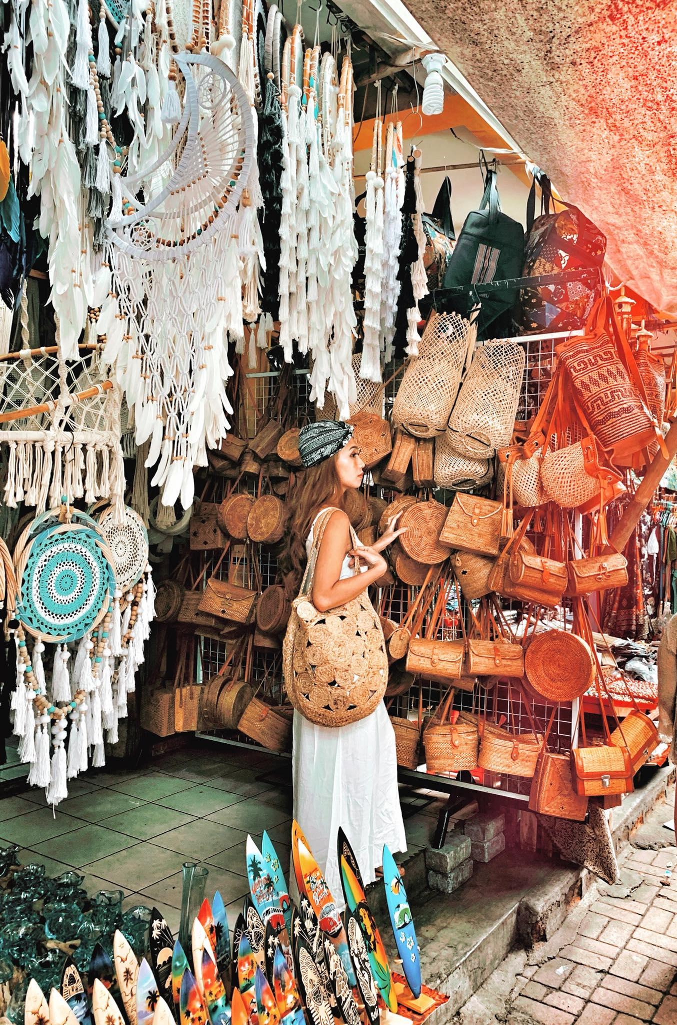 """Chợ nghệ thuật địa phương Ubud nổi tiếng là thiên đường đồ Mỹ nghệ đầy sắc màu ở Bali. Khu chợ tọa lạc tại một trong những vị trí đắc địa nhất tại trung tâm Ubud, nằm ngay trên đường Jalan Rây Ubud, cạnh Cung điện Hoàng gia Puri Saren. Khu chợ đóng một vai trò quan trọng trong đời sống xã hội và kinh tế của thị trấn Ubud.  Ở đây mọi người nhớ trả giá nha! Trả cỡ nào cũng dính. Vui nhất khoản này. Mình bị mê mấy em túi cói, dreamcatcher và đặc biệt là những """"con kiu"""" gỗ trang trí làm móc khoá, đồ khui bia cực chất!"""